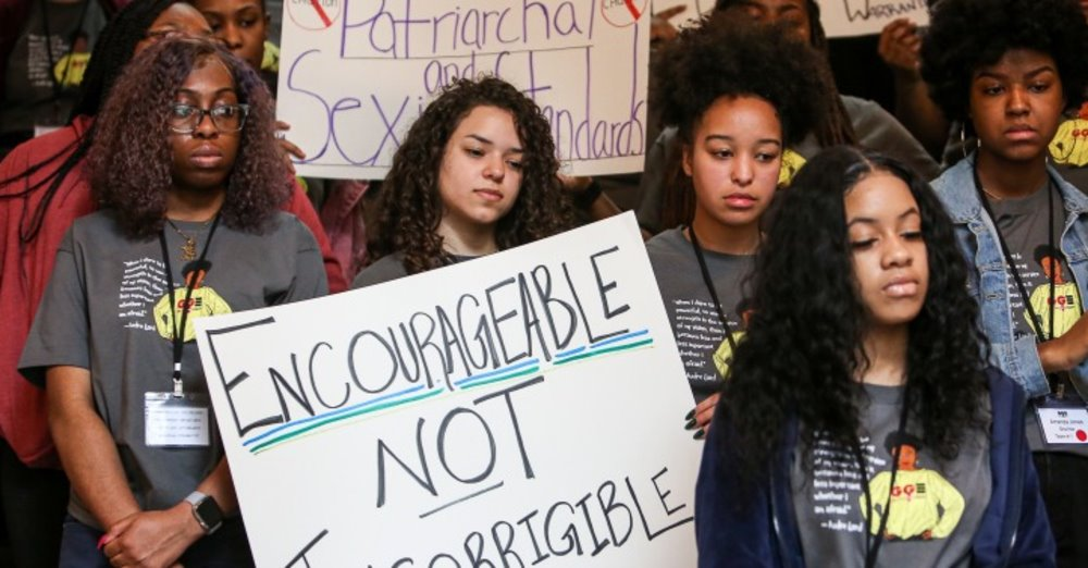 Young women from Girls for Gender Equity hold signs, one of which reads: Encourageable not Incorrigible